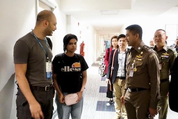 La mujer saudí, de 18 años de edad, es escoltada por un oficial de inmigración de Tailandia y miembros de Acnur en el aeropuerto internacional Suvarnabhumi, en Bangkok. Foto: AFP