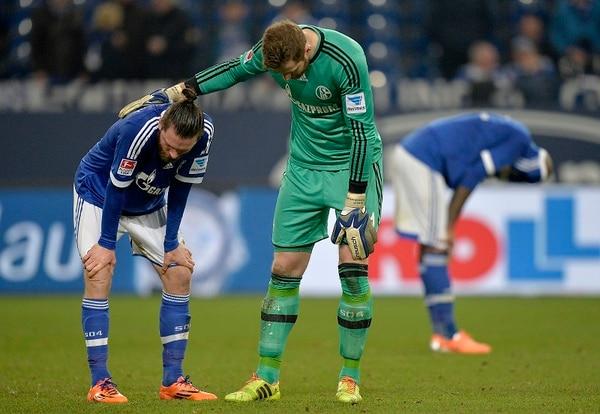 El arquero del Schalke 04, Ralf Faehrmann brinda consuelo a su compañero Tim Hoogland, luego de empatar sin goles en casa ante el Maguncia.