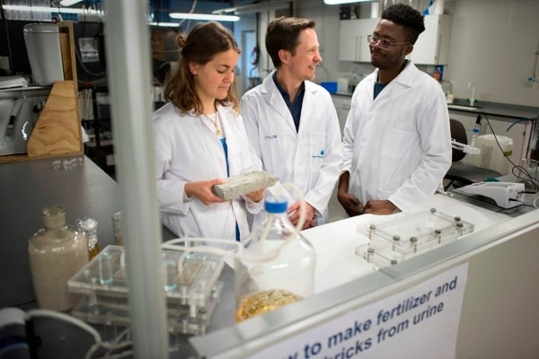 (From L) Suzanne Lambert, Dr Dyllon Randall and Vukheta Mukhari, developers of the world's first bio-brick which uses human urine as one of the binding components, show off one of their bricks in the lab at the Department of Civil Engineering at the University of Cape Town (UCT) on November 2, 2018 in Cape Town. - In one of the latest innovations in the search for eco-friendly building materials, South African university researchers have created bricks using human urine. The first of their kind in the world, the bio-bricks hold out the prospect of a sustainable alternative to standard clay and concrete bricks, they hope. (Photo by Rodger BOSCH / AFP)
