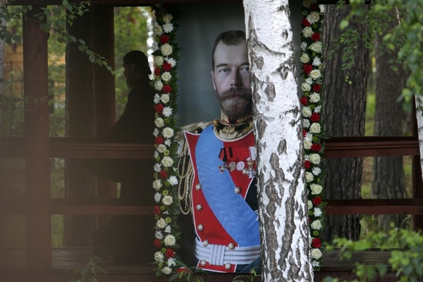 Russian Orthodox priest walks close to a portrait of the last Russian tsar, Nicholas II during as he takes part in a nightime procession marking 100 years since the Bolsheviks shot dead tsar Nicholas II and his family after he abdicated outside Yekaterinburg early on July 17, 2018. The powerful church leader led the procession that began in the early hours of July 17, from the murder site to a monastery commemorating the victims outside the city of Yekaterinburg just east of the Ural mountains. Another 20,000 people joined the commemorations when the procession arrived at the monastery in Ganina Yama after covering the distance of 21 kilometres (13 miles). / AFP PHOTO / Vlad LONSHAKOV