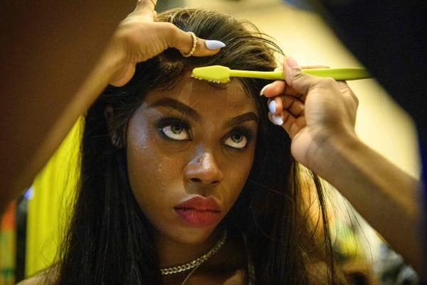 TOPSHOT - This picture taken on November 6, 2020 shows Harmony Anne-Marie Ilunga, 22, who moved to Hong Kong as a child refugee from the Democratic Republic of Congo, having her makeup applied in the backstage area before the 'Harmony IV' fashion show in Hong Kong, which aims to celebrate the city's diversity. - As a young black woman modelling in Hong Kong, Harmony Anne-Marie Ilunga rarely saw anyone who looked like her in the magazines. Now the 22-year-old is trying to change that -- one model at a time. (Photo by Anthony WALLACE / AFP)