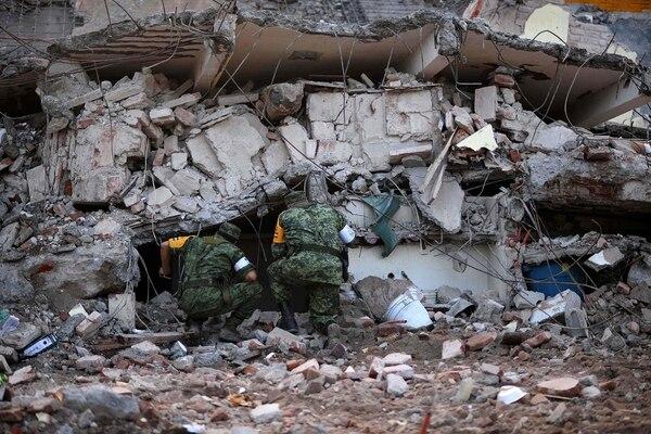 Rescatistas buscaban sobrevivientes del terremoto entre los escombros.
