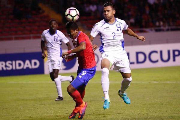 Andy Reyes disputa la pelota ante un defendor de Honduras.