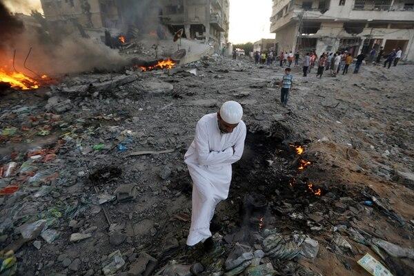 Un palestino observaba ayer entre los escombros de un área dañada por un ataque aéreo israelí en la ciudad de Gaza. Decenas de palestinos murieron ayer en otro día de la ofensiva contra Hamás. | AP