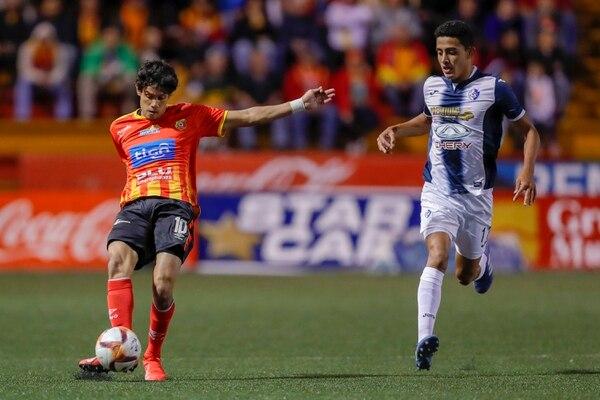 Yeltsin Tejeda pasa la pelota ante la marca de Daniel Chacón, en el duelo entre Herediano y Cartaginés. Fotografía José Cordero