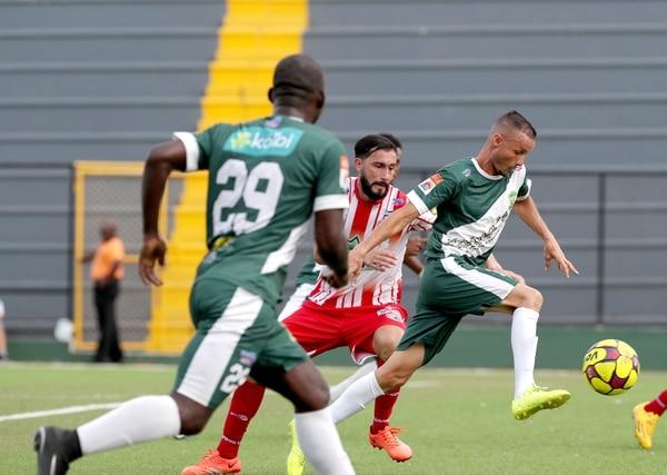 El defensor santista José Garro (rojo) intentó detener al volante limonense Alexander Espinoza (derecha).