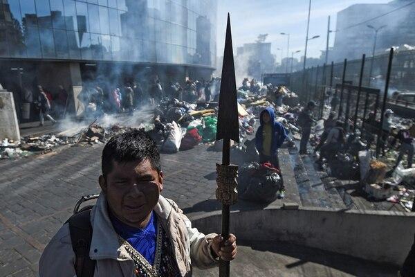 Indígenas limpian las afueras de la Casa de a Cultura en Quito, el 14 de octubre, tras promesas de acuerdos de diálogo (foto: Luis ROBAYO / AFP).