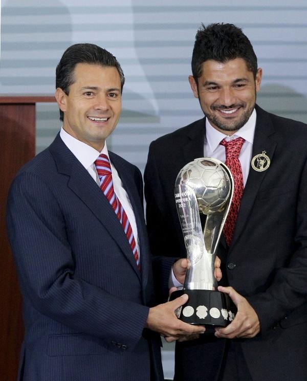 El presidente de México, Enrique Peña Nieto, le entrega un trofeo de reconocimiento a los campeones de México en el Apertura de 2012, el equipo de Tijuana. | EFE.