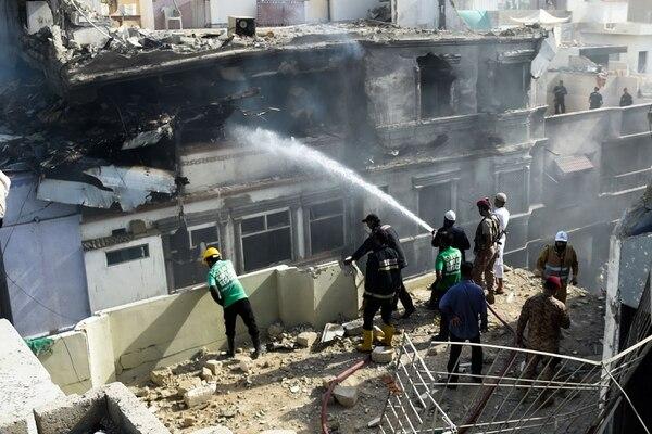 Un bombero rocía agua en un edificio quemado después de que un avión de Pakistan International Airlines se estrellara en una zona residencial de Karachi, el 22 de mayo del 2020. Foto: AFP
