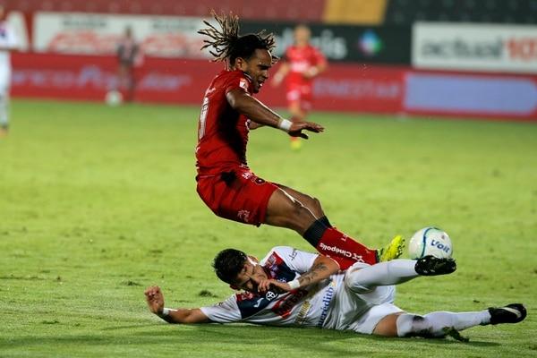 Sadier Camacho se barrió para quitarle la pelota a Jonathan McDonald, quien el sábado fue el capitán de la Liga. Foto: Mayela López