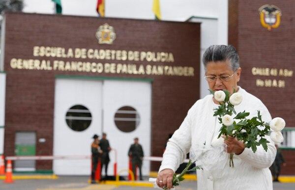 Una mujer coloca flores frente a la academia policial Francisco de Paula Santander, un día después de que explotó un coche bomba en el lugar, ubicado en Bogotá. Foto: AP
