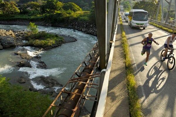 Corredores aficionados con el apoyo de sus compañeros en la buseta disfrutaron el paso por el puente sobre el río Barranca, en Puntarenas, minutos después de haber amanecido. | ADRIÁN SOTO