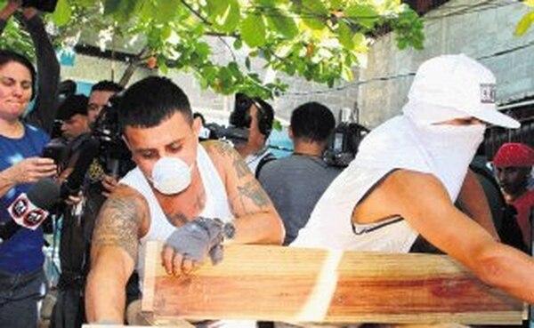 Miembros de la Mara Salvatrucha laboran en el taller de carpintería de la cárcel de San Pedro Sula. | AFP