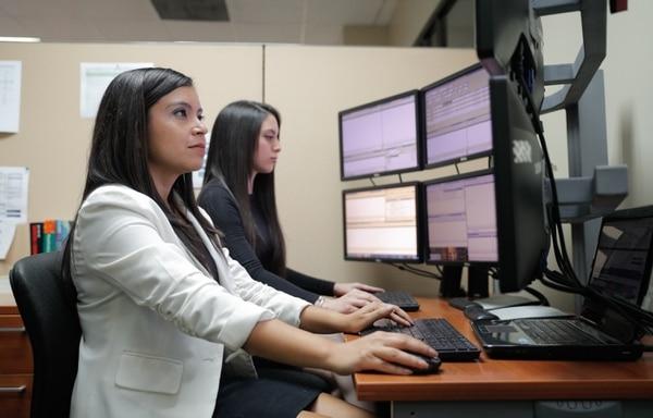 Geisel Solis (saco blanco) y Daniela Andrade (de negro) laboran en la Bolsa Nacional de Valores. El coronavirus comienza a verse reflejado también en las transacciones en esta entidad. Foto Jeffrey Zamora