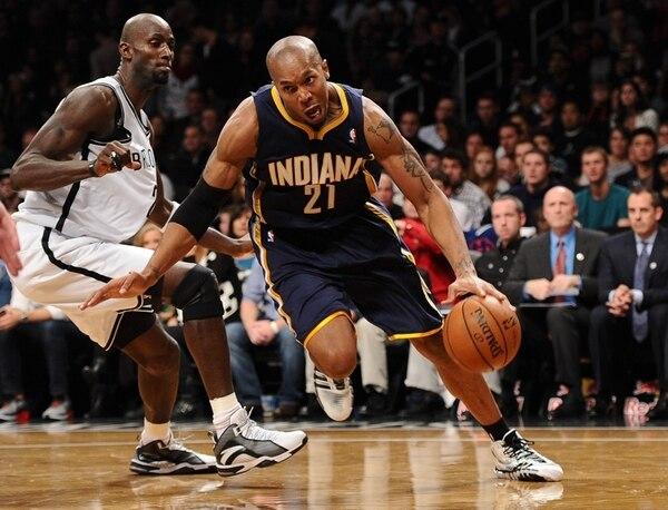 David West, de los Pacers, conduce el balón con la marcación de Kevin Garnett, de los Nets. Indiana ganó el sábado y alcanzó siete triunfos. | AFP