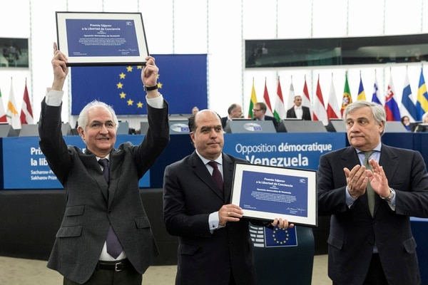 President of the Venezuelan parliament Venezuela Julio Borges, center, and ousted Caracas mayor Antonio Ledezma, left, show their award as European Parliament President Antonio Tajani applauds after they received the Sakharov Prize in Strasbourg, eastern France, Wednesday, Dec.13, 2017. The award, named after Soviet dissident Andrei Sakharov, was created in 1988 to honor individuals or groups who defend human rights and fundamental freedoms. (AP Photo/Jean-Francois Badias)