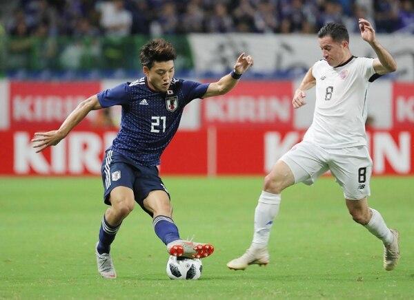 El jugador japonés Ritsu Doan (izquierda) recibe la marca del lateral izquierdo Bryan Oviedo (derecha) durante el juego de este martes. Foto: AFP