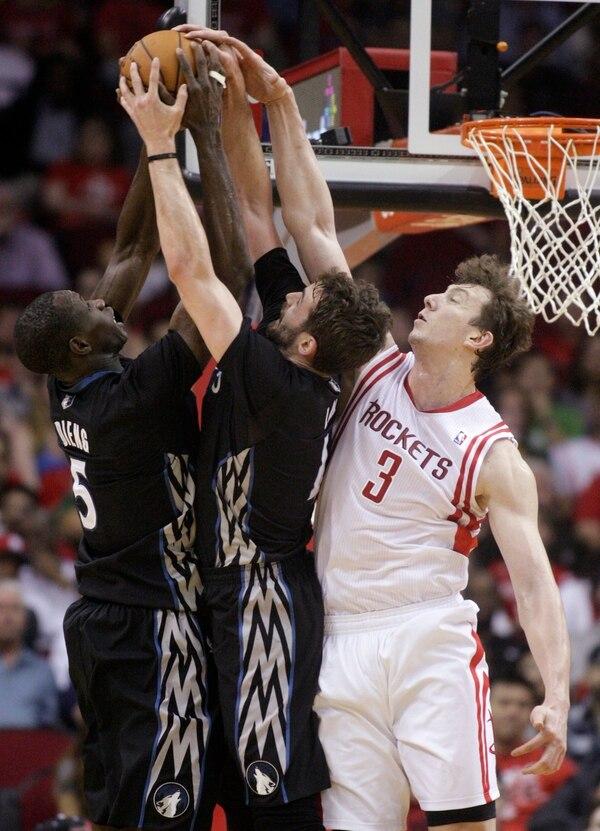 Los jugadores de los Timberwolves, Gorgui Dieng (5) y Kevin Love disputan la pelota con Omer Asik (3) de los Rockets.