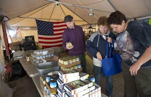 Residentes miran alimentos enlatados en un centro de acopio. | AFP
