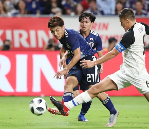 Ritsu Doan dispara ante la marca del defensor Óscar Duarte. (Photo by JIJI PRESS / JIJI PRESS / AFP) / Japan OUT