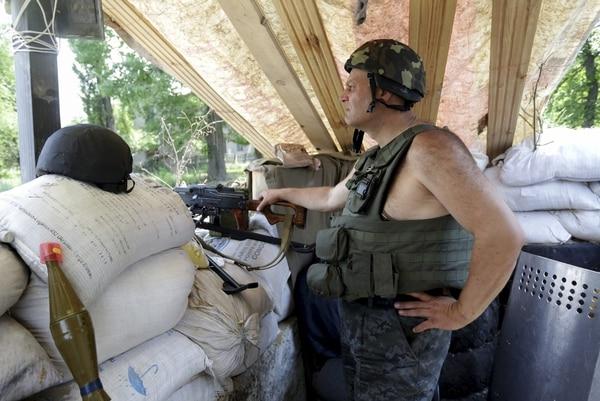 Un soldado ucraniano permanece en guardia en un puesto de control cerca de Slaviansk, Ucrania. Al menos 13 soldados y un general ucraniano murieron hoy al ser derribado el helicóptero en el que viajaban a las afueras de Slaviansk (este).