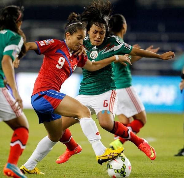 Carolina Venegas (9) renunció a su trabajo debido a que no le dieron facilidades para asistir a las prácticas o a los juegos. En la imagen enfrenta a México, en un juego eliminatorio rumbo al Mundial de Canadá. | AP