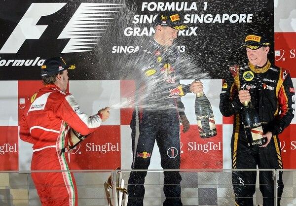 El ganador Sebastian Vettel de Alemania (al centro), el segundo clasificado, el piloto de Ferrari, Fernando Alonso, de España (izquierda) y el tercer clasificado, Kimi Raikkonen, de Finlandia (finlandia) celebran con champán en el podio después de la competencia de Fórmula.