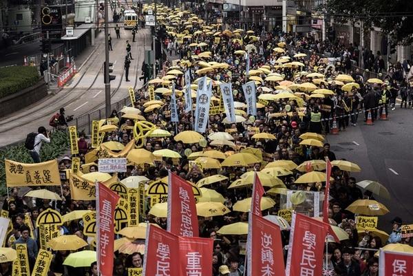 Miles de personas marcharon ayer con sombrillas amarillas en Hong Kong. Esta es la primera gran manifestación desde que estudiantes ocuparon tramos de carreteras. | AFP