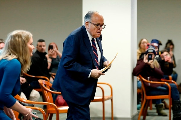 Rudy Giuliani, personal lawyer of US President Donald Trump, walks to take his seat during an appearance before the Michigan House Oversight Committee in Lansing, Michigan on December 2, 2020. - The president's attorneys, led by Rudy Giuliani, have made numerous allegations of election fraud. (Photo by JEFF KOWALSKY / AFP)