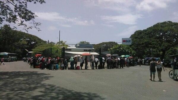 Los viajeros se tapaban del sol con sombrillas a la espera de cruzar el puesto fronterizo.