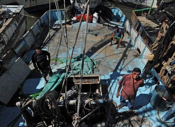 Francisco Javier Reyes (izquierda), Renzo Vásquez y Minor Bonilla a bordo del barco Capitán Bonilla, primera embarcación camaronera a la que se le venció el permiso de pesca de arrastre para la captura de camarón. Bonilla, dueño del barco, manifestó que en esta transición el apoyo estatal ha sido nulo, aunque unas 45 personas se ven afectadas directa e indirectamente. | ALBERT MARÍN.