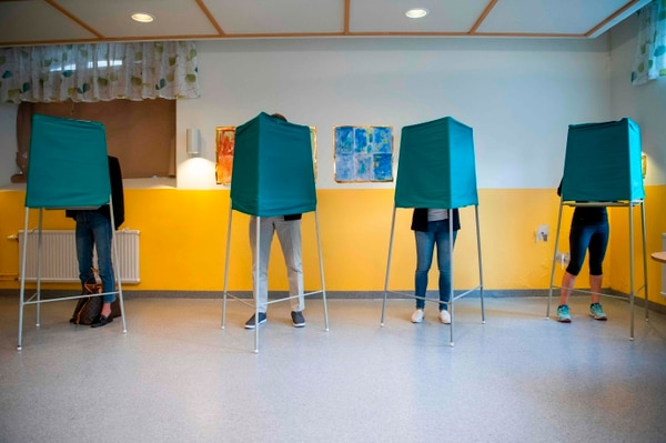 TOPSHOT - People stand on booths at a polling station during the Swedish general elections in Stockholm on September 9, 2018. - The polls opened for Swedish legislative elections today with the far-right expected to notch up a record score as voters unhappy about immigration punish one of the few remaining left-wing governments in Europe. Opinion polls suggest the anti-immigration Sweden Democrats (SD) could garner between 16 and 25 percent of the vote, making it one of the biggest parties and almost impossible to predict the make-up of the next government. (Photo by Jonathan NACKSTRAND / AFP)