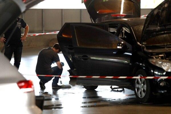 Policía forense investiga un automóvil abandonado por el ladrón armado francés Redoine Faid en el estacionamiento del centro comercial O'Parinor después de su escape a bordo de un helicóptero desde una prisión en Reau. AFP