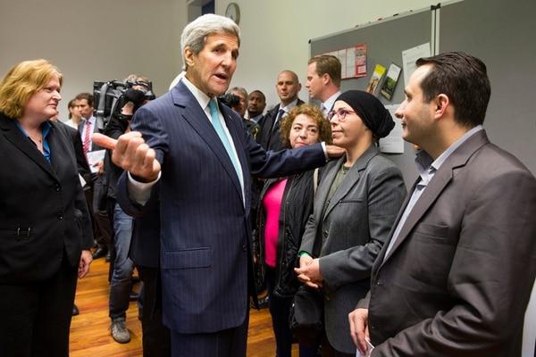 El secretario de Estado de EE. UU., John Kerry, habla con refugiados sirios en Berlín. Dijo que Rusia da armas a Siria para luchar contra EI.   AP