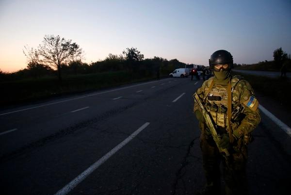 Un soldado ucraniano está de guardia en una carretera durante el intercambio de prisioneros cerca de la ciudad de Donetsk, en el este de Ucrania. Con el cumplimiento del alto el fuego, se crearía una zona desmilitarizada. | AP