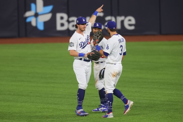 ARLINGTON, TEXAS - OCTOBER 20: Cody Bellinger #35, Mookie Betts #50 and Chris Taylor #3 of the Los Angeles Dodgers celebrate the teams 8-3 victory against the Tampa Bay Rays in Game One of the 2020 MLB World Series at Globe Life Field on October 20, 2020 in Arlington, Texas. Ronald Martinez/Getty Images/AFP == FOR NEWSPAPERS, INTERNET, TELCOS & TELEVISION USE ONLY==
