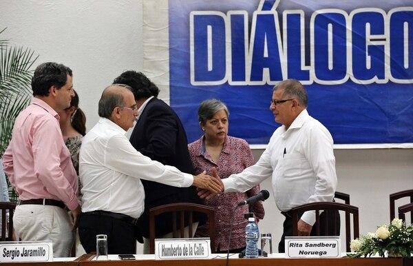 El jefe del equipo negociador del gobierno, Humberto de la Calle (izq.) saluda al comandante de las FARC Rodrigo Granda (d) durante la lectura de un comunicado conjunto el jueves en La Habana. | EFE