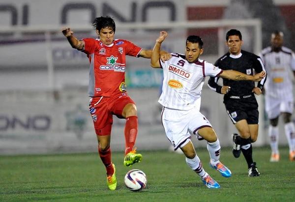 Carlos Hernández (izquierda), quien anotó la noche de este miércoles para Santos, disputó el balón en esta jugada con el morado Diego Estrada.