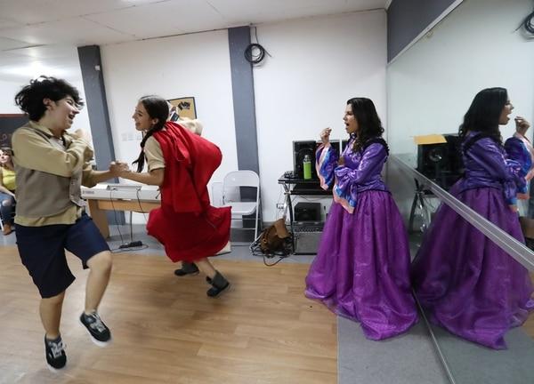 Sofía Salazar (izquierda) baila como el personaje de Jack junto a Andrea Somogyi, quien interpreta a Caperucita Roja. La profesora Iriabelle González (derecha) dirige el canto. John Durán