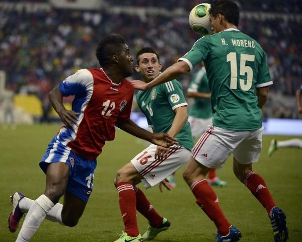El delantero costarricense Joel Campbell intenta eludir la marca del mexicano Hector Moreno. | AFP