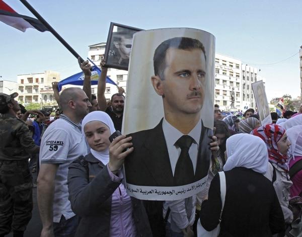 Miles de simpatizantes del presidente Bashar al-Asad, algunos portando retratos de él, participaron ayer en una concentración en Damasco. | EFE