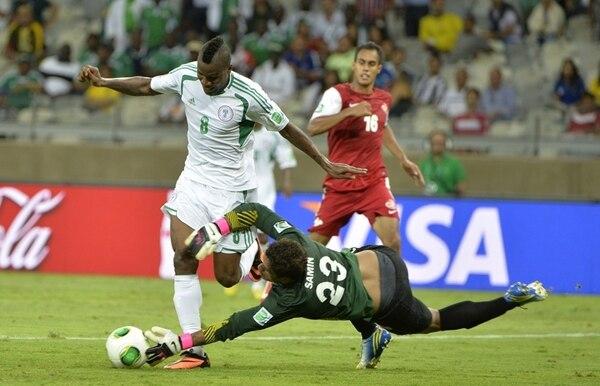 El nigeriano Brown Ideye (8) intenta esquivar la salida del portero de Tahití, Xavier Samin.
