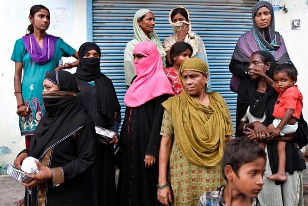 Residentes de una zona afectada por inundaciones esperaban ayer la llegada de alimento en Allahabad, India.   AP.