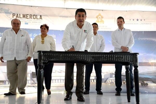 El presidente de Honduras, Juan Orlando Hernández, firma los documentos durante un acto en la base militar Enrique Soto Cano en Palmerola, 80 km al norte de Tegucigalpa. En el sitio de la base, que en la actualidad alberga aviones militares de Honduras y EE. UU., se construirá el aeropuerto internacional de Palmerola, con una pista de 2.440 metros de largo a un costo de $163 millones.