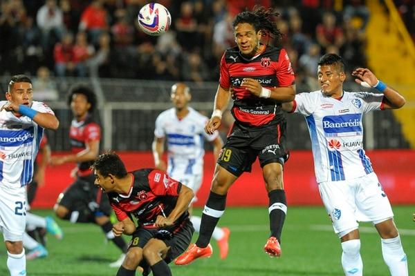El ariete rojinegro Jonathan McDonald cabecea la pelota acechado por el brumoso José Leiva. Lezcano y Alonso observan. | LUIS NAVARRO