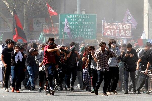 Miles de estudiantes chilenos son alcanzados por gases arrojados por la policía antidisturbios este jueves 21 de abril, durante la primera manifestación del año en contra de la reforma educativa, en Santiago de Chile.