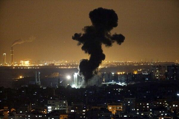 Arriba: Israelíes rescatan objetos de una casa de parientes que fue golpeada por un cohete lanzado desde la franja de Gaza hacia la ciudad de Beersheba, en el sur de Israel. Abajo: El humo sale de edificios en la ciudad de Gaza luego de un bombardeo de la aviación israelí. | AP, AFP