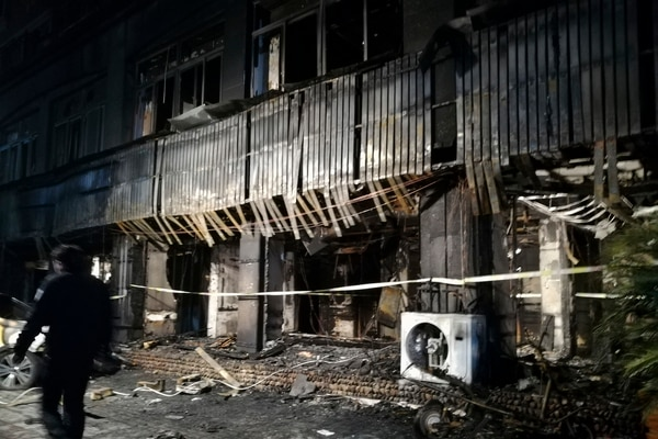 In this photo released by Xinhua News Agency, a man walks past the Zuxintang Foot Massage Parlor damaged by a fire in Tiantai County, east China's Zhejiang Province, Monday, Feb. 6, 2017. The fire at the massage parlor on Sunday killed and injured dozens of people, state media reported. (Wang Junlu/Xinhua via AP)
