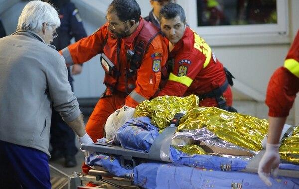 Una mujer con quemaduras en el rostro fue atendida ayer por paramédicos debido al incendio de una discoteca en Bucarest, Rumanía.   EFE