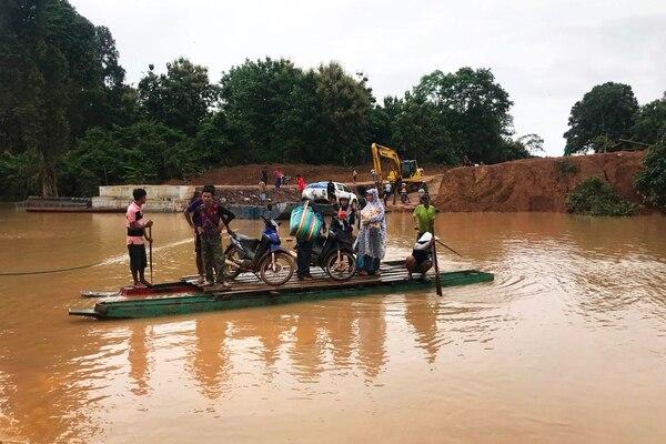 Afectados por las inundaciones causadas por la ruptura de una presa en Laos usaban una embarcación artesanal para cruzar el río Xe Khong, en la provincia de Attapeu, el miércoles 25 de julio del 2018.
